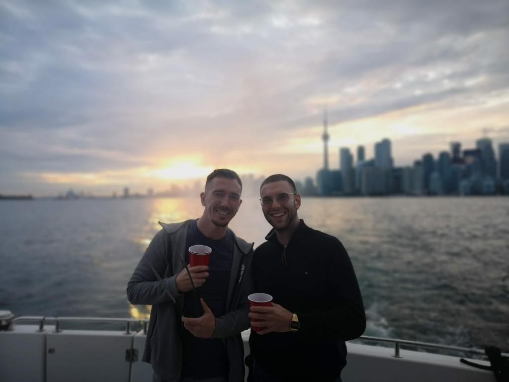 ContactMonkey employees holding party cups on a boat at sunset